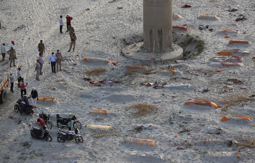 Policías junto a varios cuerpos enterrados en tumbas poco profundas a orillas del Ganges,\