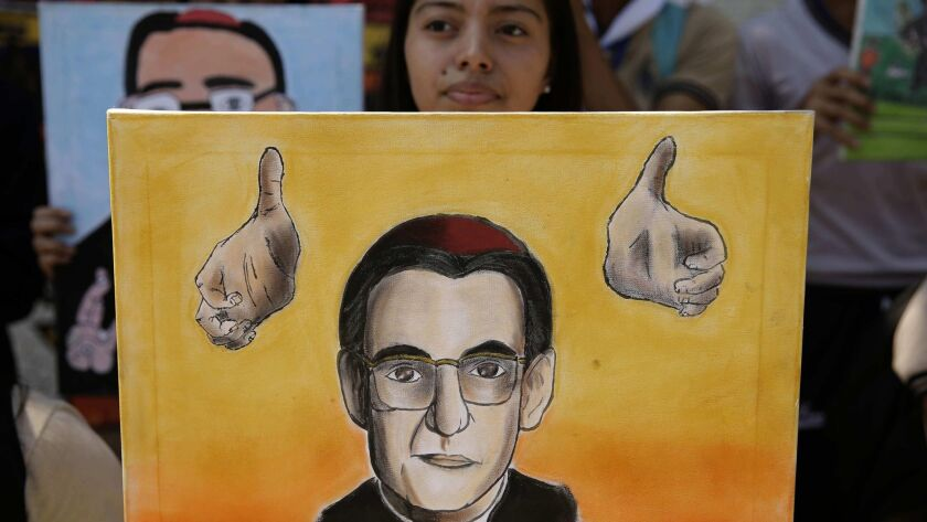 A youth holds a portrait of slain Archbishop Oscar Romero of El Salvador after the Vatican's announcement on March 7, 2018, that he will be canonized.