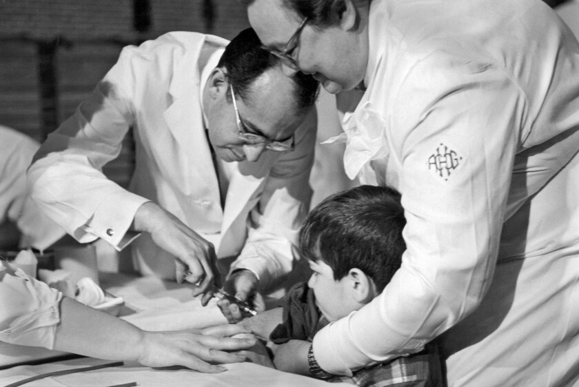Dr. Jonas Salk gives a vaccination