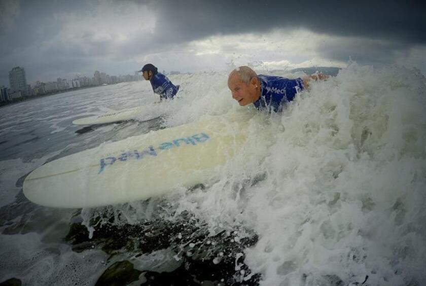 Francisco Verazani de Aguiar, 74, enjoys surfing during a class taught by the Radical School on Jan. 22, 2019, on the beach at Santos, Brazil. EFE-EPA/Fernando Bizerra Jr