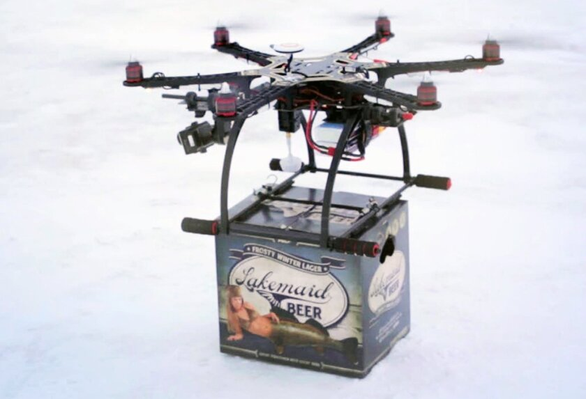 In this Jan. 16, 2014 image from video provided by Lakemaid Beer, a mini-drone lands with a 12-pack of beer for ice fishing anglers on Minnesota's Lake Mille Lacs. Lakemaid president Jack Supple said he thought Amazon's package delivery plan would better be applied on a wide open frozen lake where