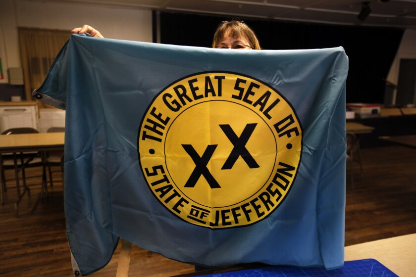 A woman holds a banner with the seal of a secession effort in 1941 that involved rural counties in Oregon and California.