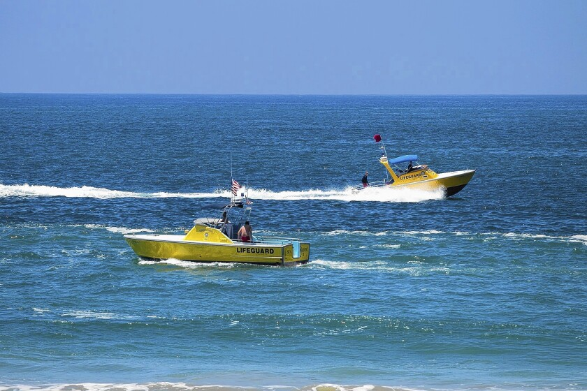 Lifeguard boats patrol the shores on Wednesday in Newport Beach.