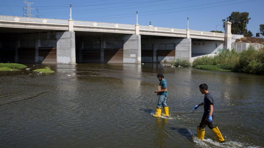 L.A. Trade Tech students John Silva, left, and Christopher Zamora wade into the L.A. River for water