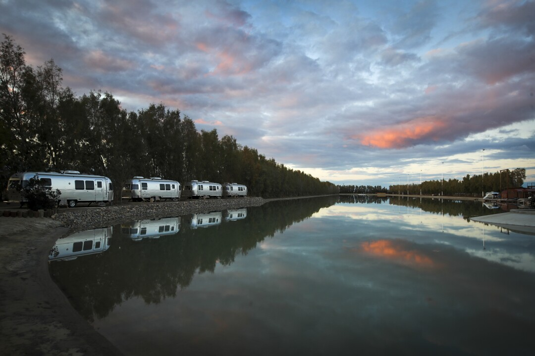 The sun sets over Airstream campers overlooking a lake next to the wave pool