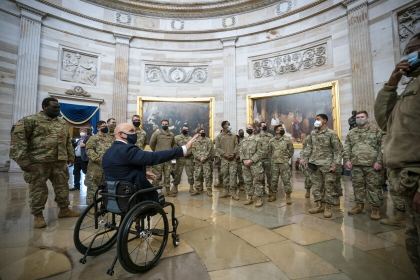 Rep. Brian Mast, R-Fla., left, visits with National Guard troops who are helping with security at the Capitol Rotunda.