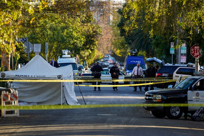 Yellow crime scene tape crosses a street where police officers are standing and a tent is set up.