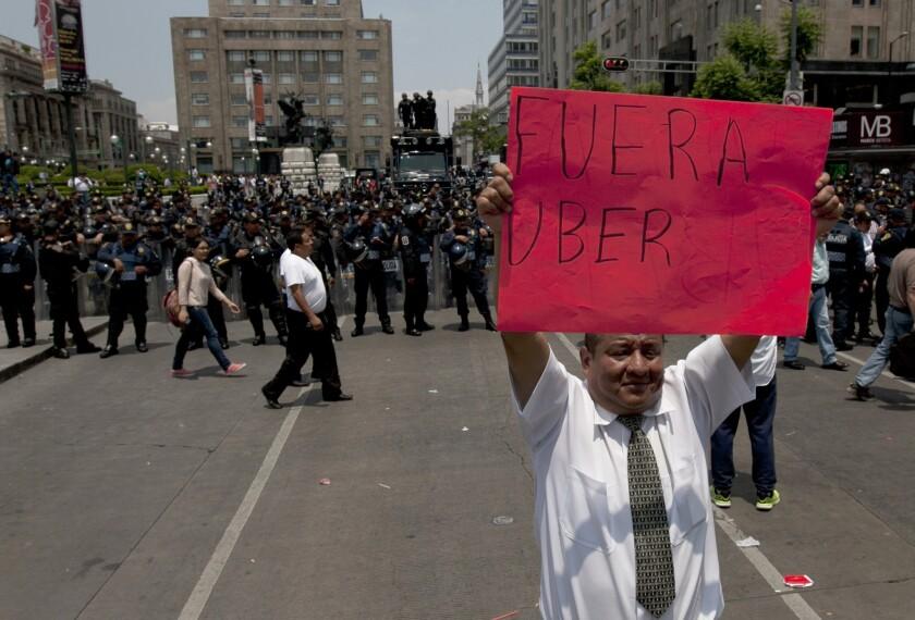"""En esta foto, un hombrre alza el cartel de """"fuera uber"""" frente a la policía antimotines durante una marcha por una avenida principal de la ciudad de México. Los taxistas exigen a las autoridades que arresten a los conductores de Uber e incauten sus autos. Pero Uberr sigue creciendo debido en parte al pésimo servicio que brindan los taxis tradicionales."""