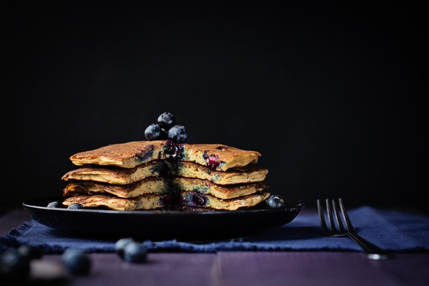 A plate of stacked blueberry pancakes.