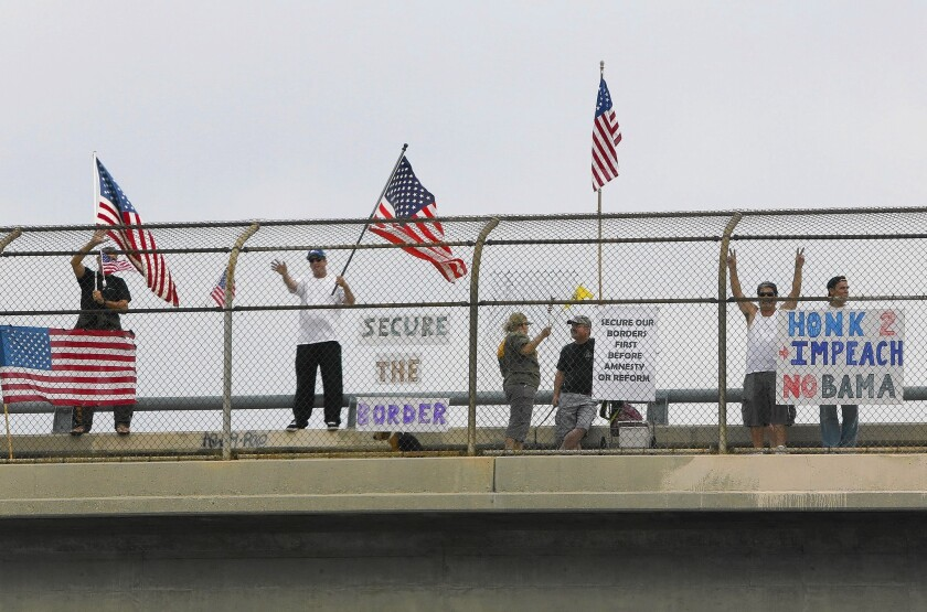Protesters wave to motorists on the Wardlow Road overpass of the 605 Freeway in Long Beach on Saturday.