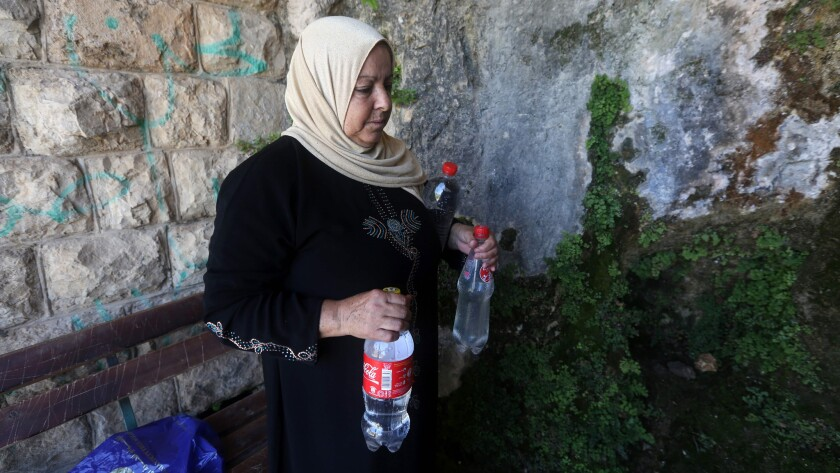 A member of the Salim family carries bottles filled with spring water on June 23 in Salfit, north of Ramallah, where some of the West Bank village's inhabitants have been without water for days.