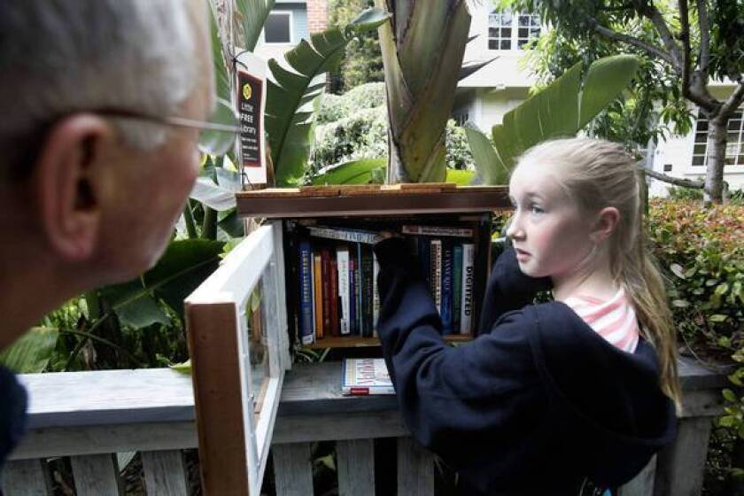 Fiona Sassoon, 10, gets some neighborly advice from David Dworski, left, on book selections at Dworski's diminutive outdoor library in Venice.