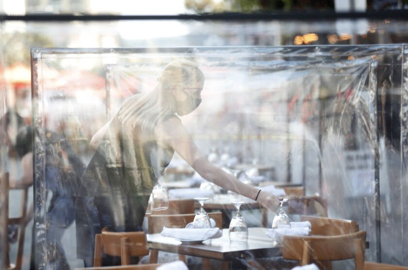 Lindsey Burkett sets a table at the Butcher's Cut Steakhouse outdoor seating area