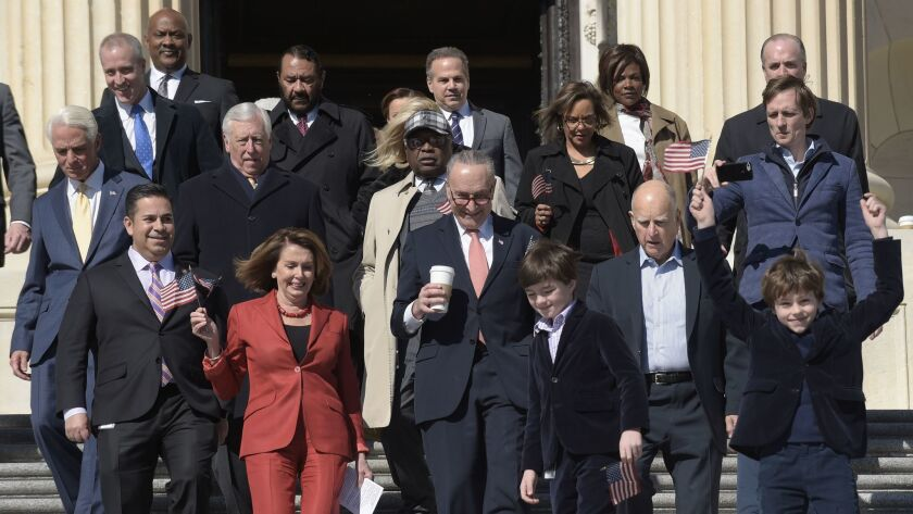 House Minority Leader Nancy Pelosi (D-San Francisco), front left in red, Senate Minority Leader Charles E. Schumer (D-N.Y.) and Gov. Jerry Brown are joined by other Democrats at the U.S. Capitol for a rally marking seven years of the Affordable Care Act.