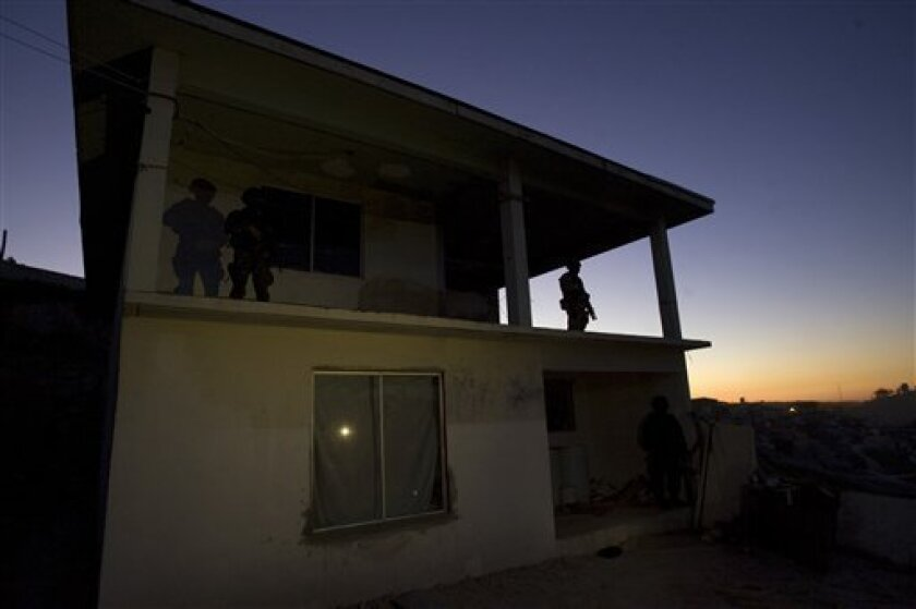 Mexican soldiers stand on guard at a house where marijuana plants being grown were found in Tijuana, Mexico, Thursday, Jan. 15, 2009.  Special forces soldiers found some 170 marijuana plants, in a room used as a greenhouse, and detained a suspect. (AP Photo/Guillermo Arias)