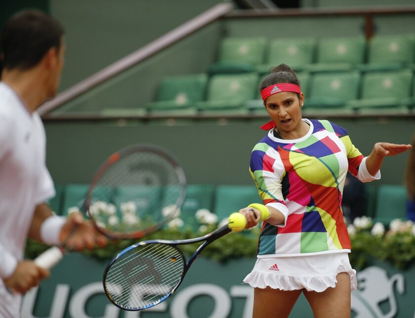 India's Sania Mirza, right, and Croatia's Ivan Dodic return the ball in the final of the mixed doubles match of the French Open tennis tournament against Switzerland's Martina Hingis and India's Leander Paes at the Roland Garros stadium in Paris, France, Friday, June 3, 2016. (AP Photo/Alastair Gra
