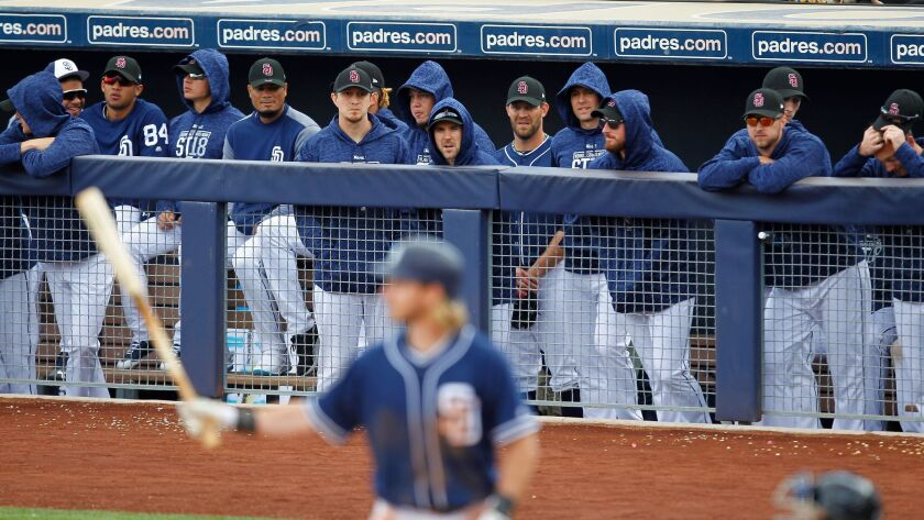 Padres players stay bundled up during a cold spring training game against the Seattle Mariners on Friday.