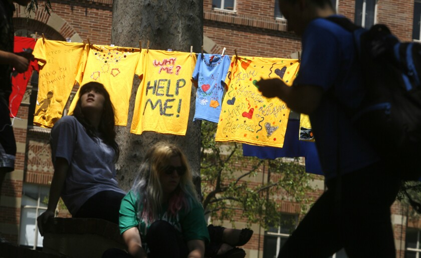 In the Clothesline Project at UCLA, survivors of domestic violence make yellow shirts to raise awareness of gender violence. Courtney Kiehl, left, sits near the line of shirts as other students pass by the display in 2011.