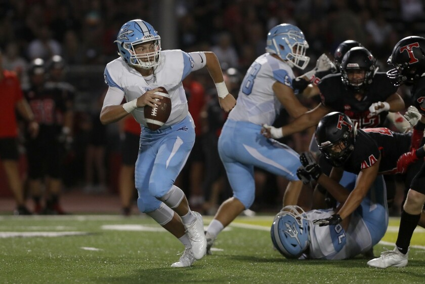 Corona del Mar High quarterback Ethan Garbers scrambles out of the pocket in the first half of a nonleague game at San Clemente on Sept. 14, 2018.