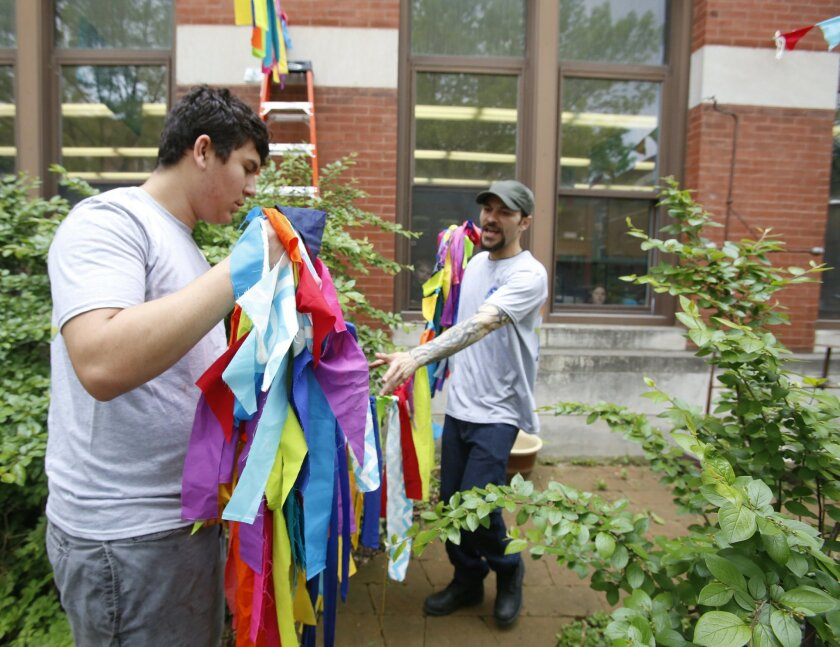 In this Friday, May 15, 2015 photo, Boy Scout David Fite, 15, prepares to hang hand-made cloth streamers with volunteer Carlos Pabon outside the Nettelhorst School in Chicago. With the help of Pabon and others, David decorated the street scene in preparation for the city's nearby Gay Pride Parade.