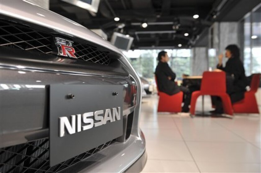 Visitors chat by a new Nissan GT-R at the Nissan Motor Co. gallery at Nissan head office in Tokyo Thursday, Jan. 8, 2009. The Japanese carmaker is likely to post an operating loss in the current fiscal year, reports said Thursday, Jan. 15, 2009. (AP Photo/Katsumi Kasahara)