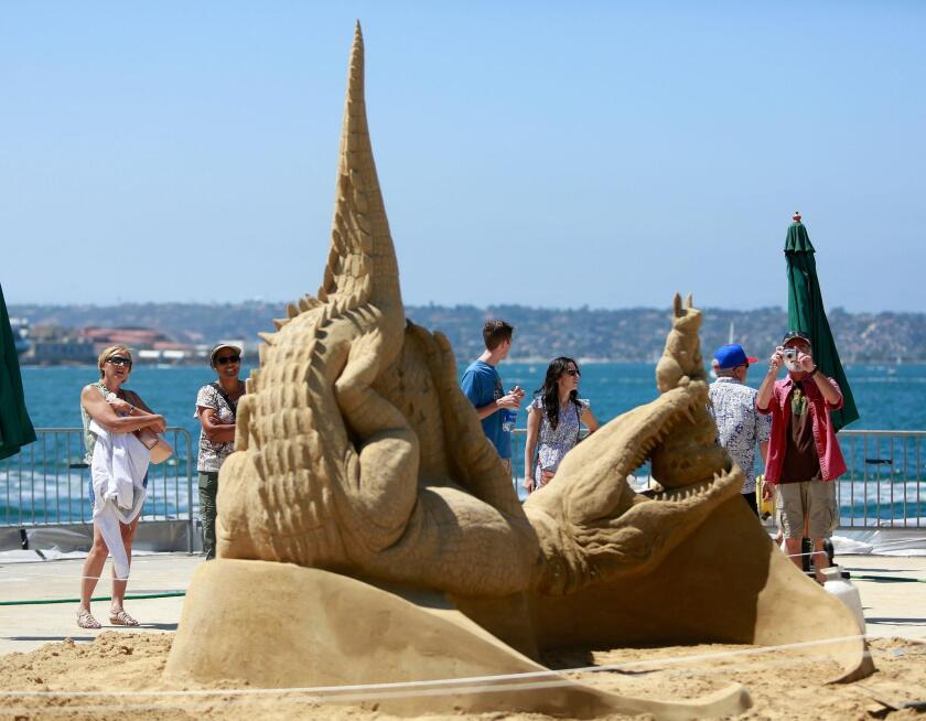 Attendees admire a sand sculptures on display at the U.S. Sand Sculpting Challenge at B Street Pier in downtown San Diego.