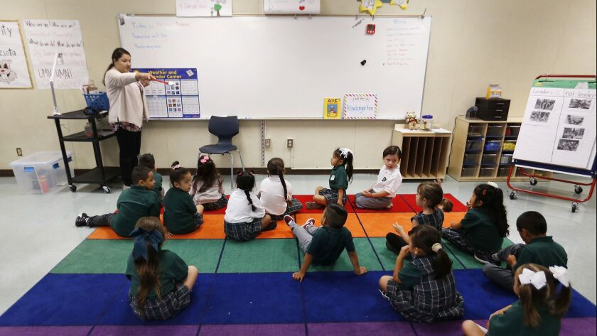 A kindergarten teacher works with students in Los Angeles on August 13.