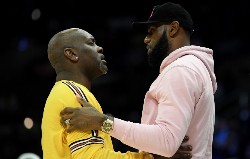 Former NBA star Gary Payton greets LeBron James.