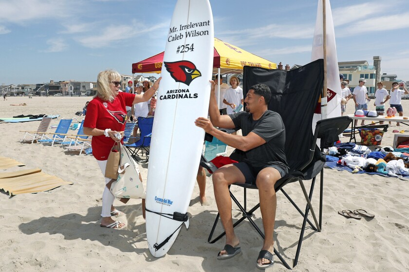 Irrelevant Week CEO Melanie Salata-Fitch, left, hands 2019 Mr. Irrelevant Caleb Wilson his honorary surfboard during the second day of the Irrelevant Week festivities in Newport Beach on June 29, 2019.