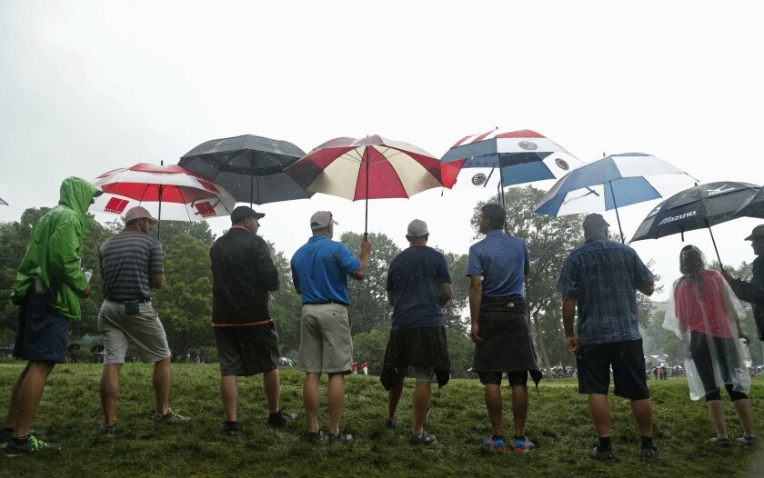 Fans wait in the rain along the first fairway for golfers during the final round of the PGA Championship golf tournament at Baltusrol Golf Club in Springfield, N.J., Sunday, July 31, 2016. (AP Photo/Mike Groll)