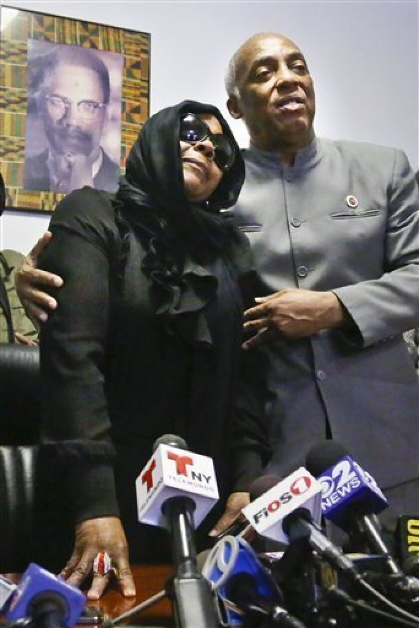 """Carol Gray, left, leans on City Councilman Charles Barron, during a press conference on Thursday, March 14, 2013 in the East Flatbush neighborhood of Brooklyn, N.Y. Gray's son Kimani """"Kiki"""" Gray, 16, was shot to death on a Brooklyn street last Saturday night by plainclothes police officers who say the youth pointed a .38-caliber revolver at them, while Gray's family says he was unarmed. (AP Photo/Bebeto Matthews)"""