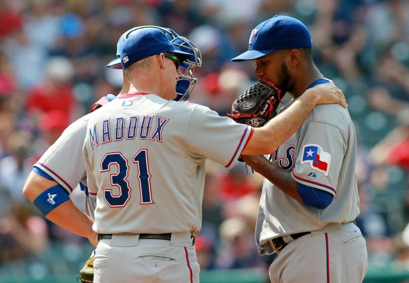 Texas Rangers pitching coach Mike Maddox (31) talks with pitcher Neftali Feliz during the ninth inning of a baseball game against the Cleveland Indians, Sunday, Aug. 3, 2014, in Cleveland. (AP Photo/Aaron Josefczyk)