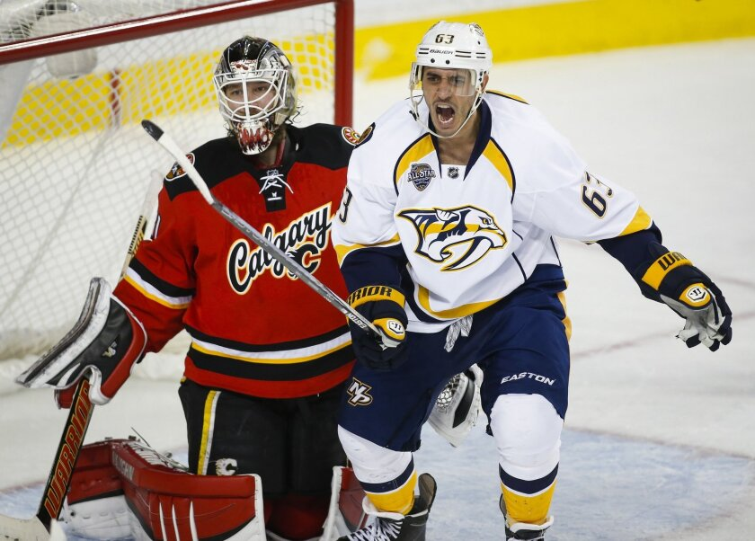 Nashville Predators' Mike Ribeiro, right, celebrates the second goal on a shot from teammate Shea Weber as Calgary Flames goalie Karri Ramo, from Finland, looks on during second period NHL hockey action in Calgary, Alberta, Wednesday, Jan. 27, 2016. (Jeff McIntosh/The Canadian Press via AP) MANDATORY CREDIT