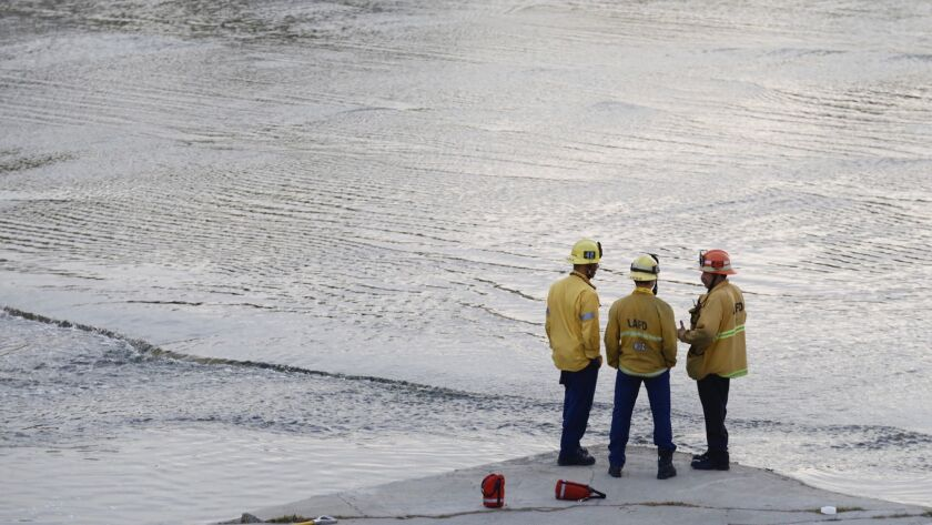 Firefighters look for a 13 year old boy at the LA River near Griffith Park Sunday, April 1. The boy