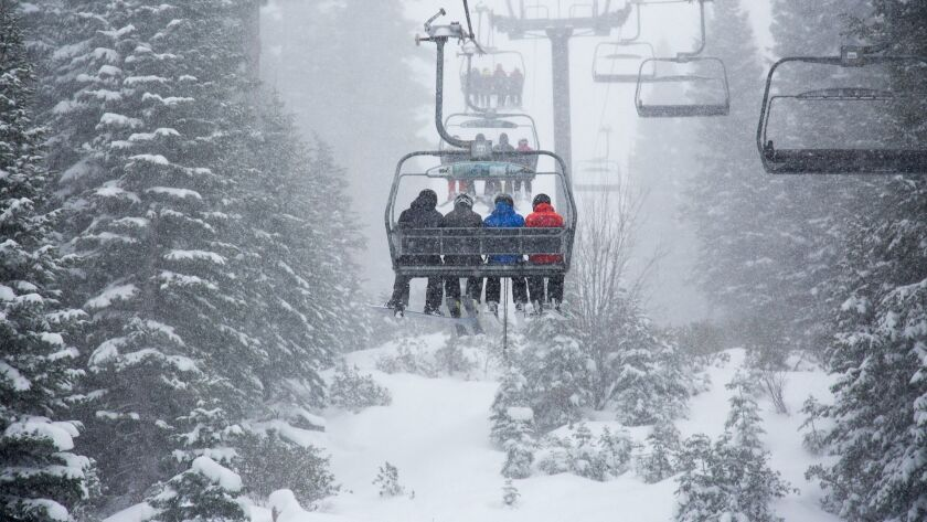 Skiers at Northstar California ride a chairlift through heavy snowfall.