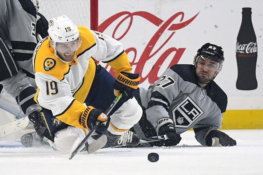 Predators center Calle Jarnkrok passes the puck as he and Kings defenseman Alec Martinez fall to the ice Jan. 4, 2020.