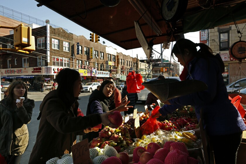 SUNSET PARK, NEW YORK--APRIL 4, 2018--Customers buy fruit along 8th Ave.at 54th St. in Sunset Park.