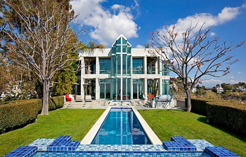 The swimming pool captures the reflection of the contemporary house, listed for $10.9 million.