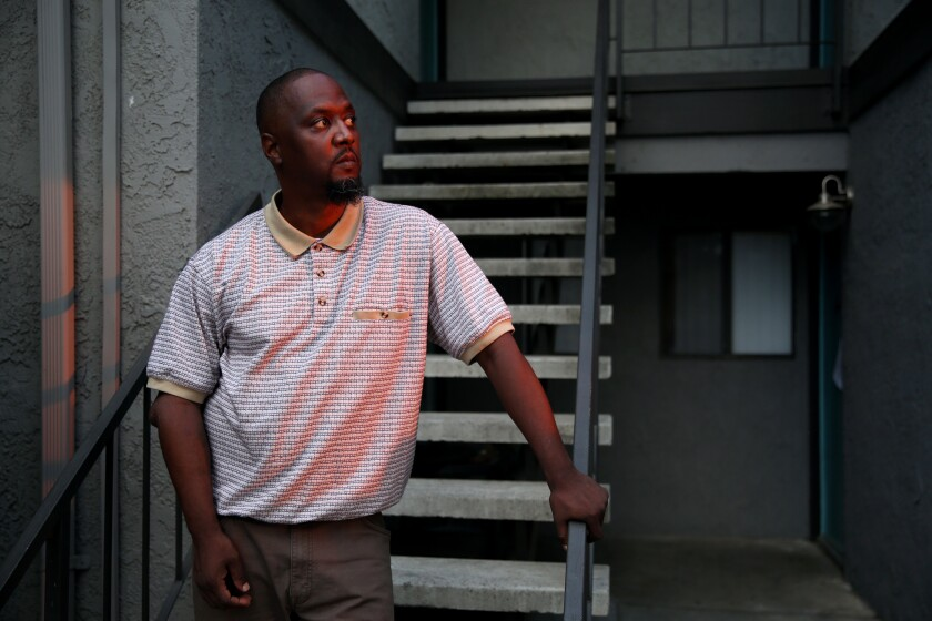 Terrance Stewart stands for a portrait outside the apartment where he has lived with his family in Colton, Calif.
