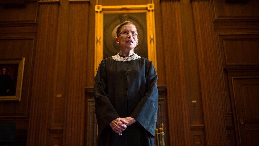 Justice Ruth Bader Ginsburg poses for a portrait standing in a wood-paneled conference room in the Supreme Court