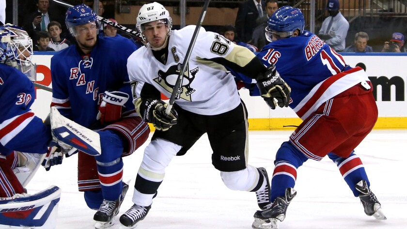 Pittsburgh Penguins captain Sidney Crosby, center, skates between New York Rangers teammates Derick Brassard, left, and Anton Stralman as goalie Henrik Lundqvist looks on during the Penguins' win in Game 4 of the Eastern Conference semifinals Wednesday.
