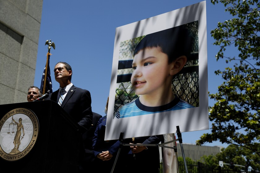 Orange County Dist. Atty. Todd Spitzer stands next to a giant photo of Aiden Leos.