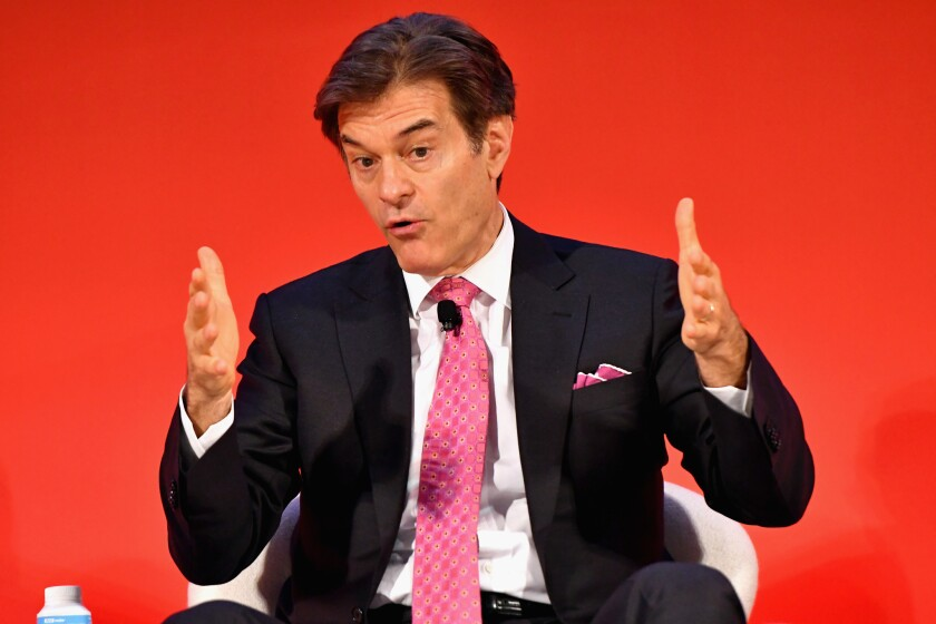 Dr. Mehmet Oz gestures with his hands while wearing a dark suit and pink tie.