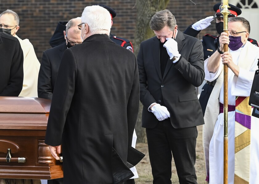 Hockey hall-of-fame legend Wayne Gretzky, right, watches the casket of his father, Walter Gretzky, as it is carried from the church during a funeral service in Brantford, Ontario, Saturday, March 6, 2021. Walter Gretzky, also known as Canada's hockey dad was 82 years old. (Nathan Denette/The Canadian Press via AP)