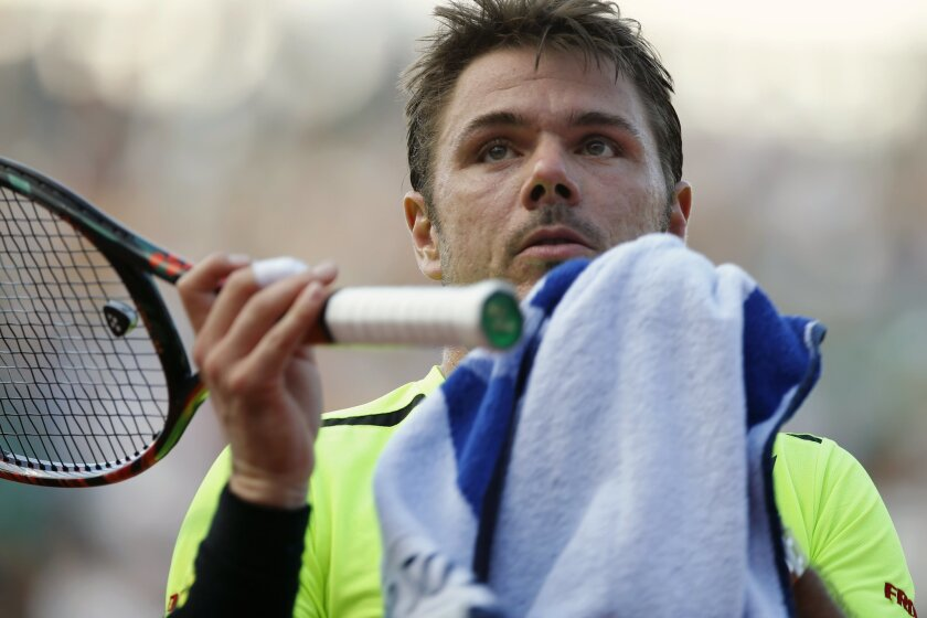 Switzerland's Stan Wawrinka dries off his racket in his third round match of the French Open tennis tournament against at the Roland Garros stadium in Paris, France, Friday, May 27, 2016. (AP Photo/Alastair Grant)