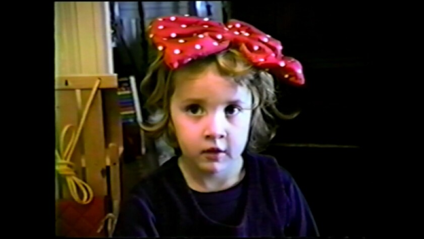 """A young Dylan Farrow, with a red and white polka dot bow in her hair, captured on camcorder in HBO's """"Allen v. Farrow."""""""