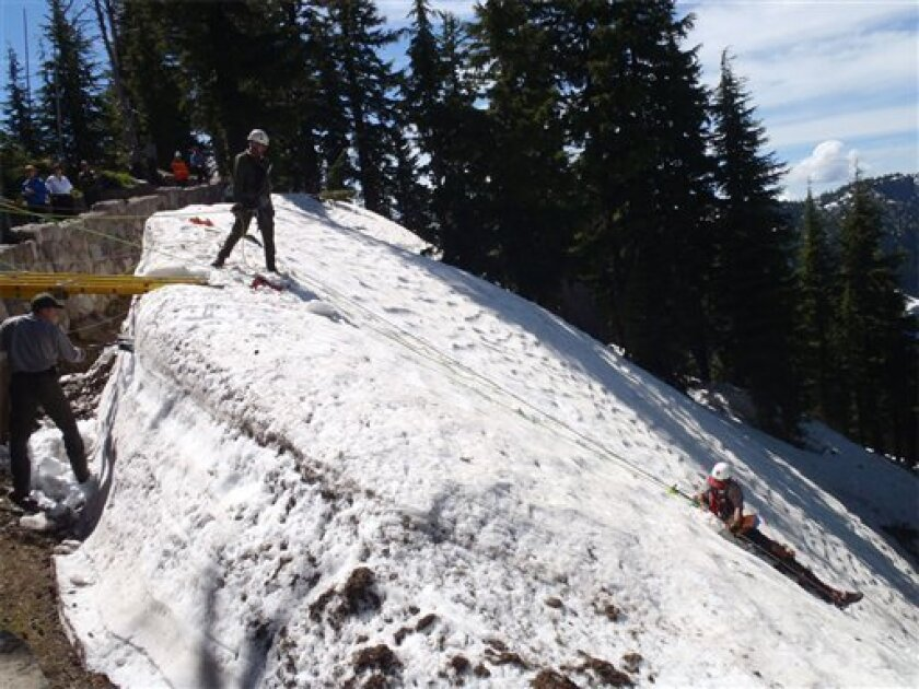 This photo taken July 11, 2011, provided by the National Park Service, shows a National Park ranger, right, helping to rescue a man who slid 300 feet in Crater Lake, Ore. Rangers and others at Crater Lake National Park spent about six hours rescuing a New York man who slid 300 feet into the remains of a volcano that forms the nation's deepest and clearest lake. The man wasn't identified. (AP Photo/National Park Service)