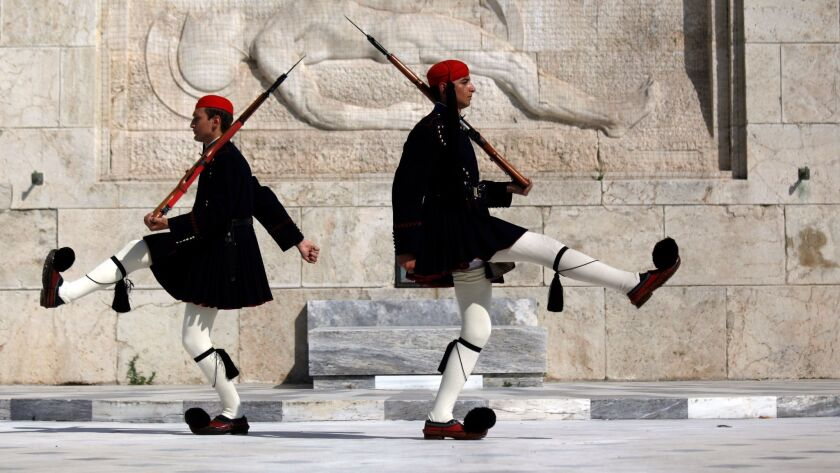 Greek guards march at the monument of the unknown soldier in front of the parliament in Athens.