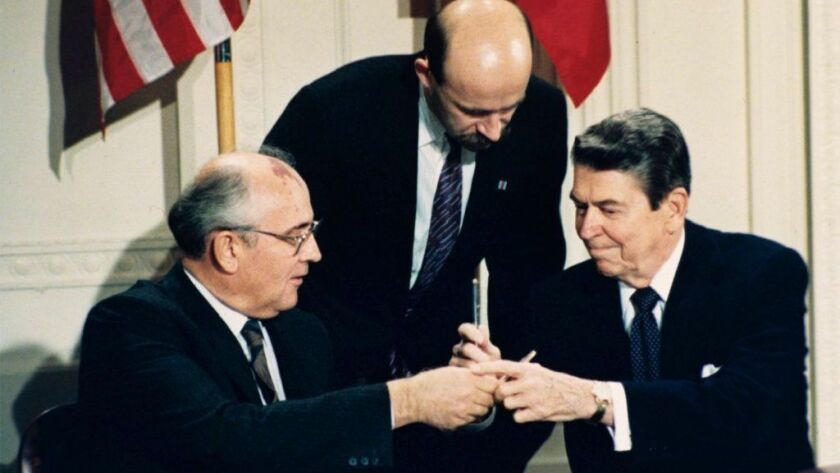 President Reagan and Soviet leader Mikhail Gorbachev, with Gorbachev's translator in the middle, participate in an INF treaty signing ceremony at the White House on Dec. 8, 1987.