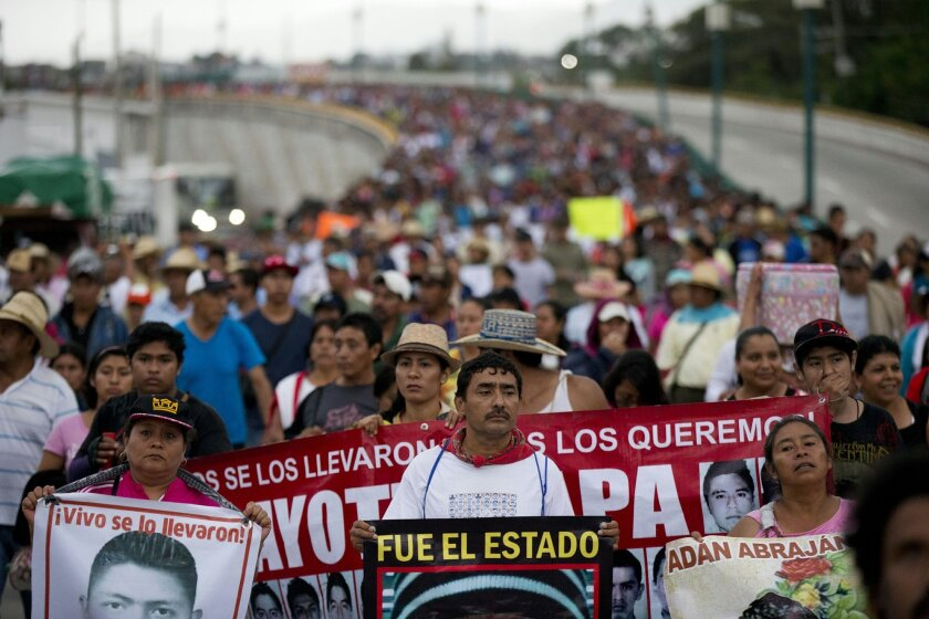 FILE - In this Saturday, Sept. 26, 2015, file photo, relatives of the 43 missing Ayotzinapa teachers' college students lead a march marking the one-year anniversary of the students' disappearances in Chilpancingo, Mexico. In a document released Sunday, Nov. 8, 2015, Mexico's National Human Rights C